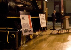 Director Courtney Wilson and Affiliations staff Jennifer Brundage in front of the fireless locomotive.