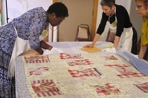 After examining a century-old quilt brought in by Birmingham resident Nora Bell (not pictured), Renee Anderson (left), from the National Museum of African American History and Culture, and textile historian Susan Neill offered tips for preserving and storing the family heirloom.