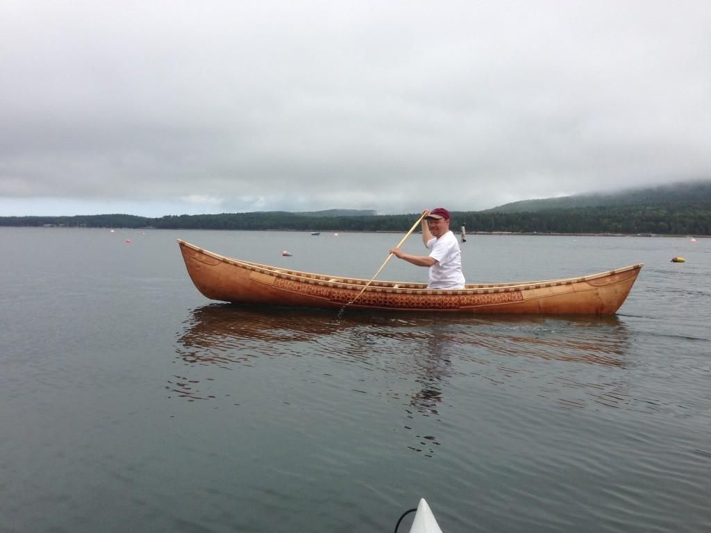 Smithsonian educator Tim Grove paddles in the Abbe Museum's homemade canoe in Maine.