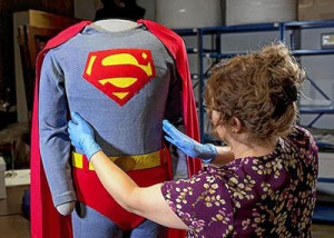 Lesley Poling, registrar of collections for the Ohio History Connection, fine-tunes the Superman costume worn by George Reeves. It will be on display through Jan. 3 at the Ohio History Center.