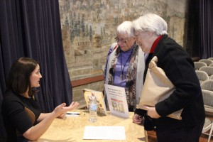 SI curator Mary Savig signs her book and talks with visitors to RIHS about artists' handmade holiday cards.