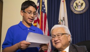 A Muslim American child reads a letter from a Japanese internment camp victim, with Rep. Mike Honda. (Courtesy of Frank Chi)