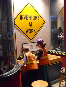 Two children lean over a Spark!Lab activity table. A yellow diamond shaped sign above them reads Inventors At work.