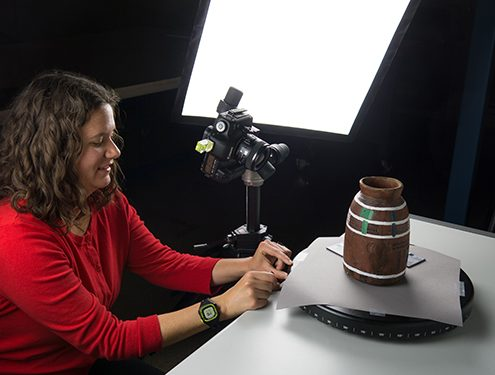 Affiliate Visiting Professional seated in a photography studio arranging a vessel on a table to be photographed.