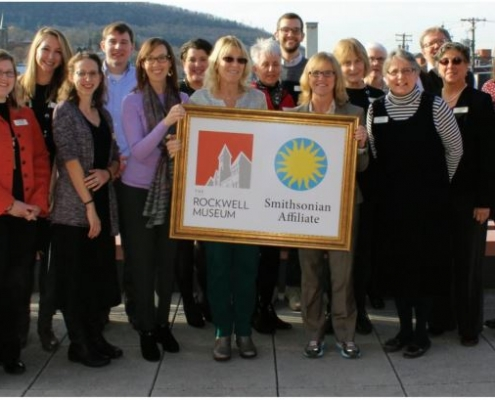 Rockwell museum staff pose with Smithsonian and Rockwell logos.