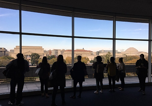 Eight people take photos of the National Mall while standing at a room-length window.