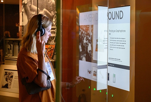 A woman with blond shoulder length hair wears headphones and stands in front of an interactive display about American Sound at the National Museum of American History.