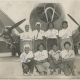 Black and white photograph depicting eight african american women posing in two rows in front of an airplane.