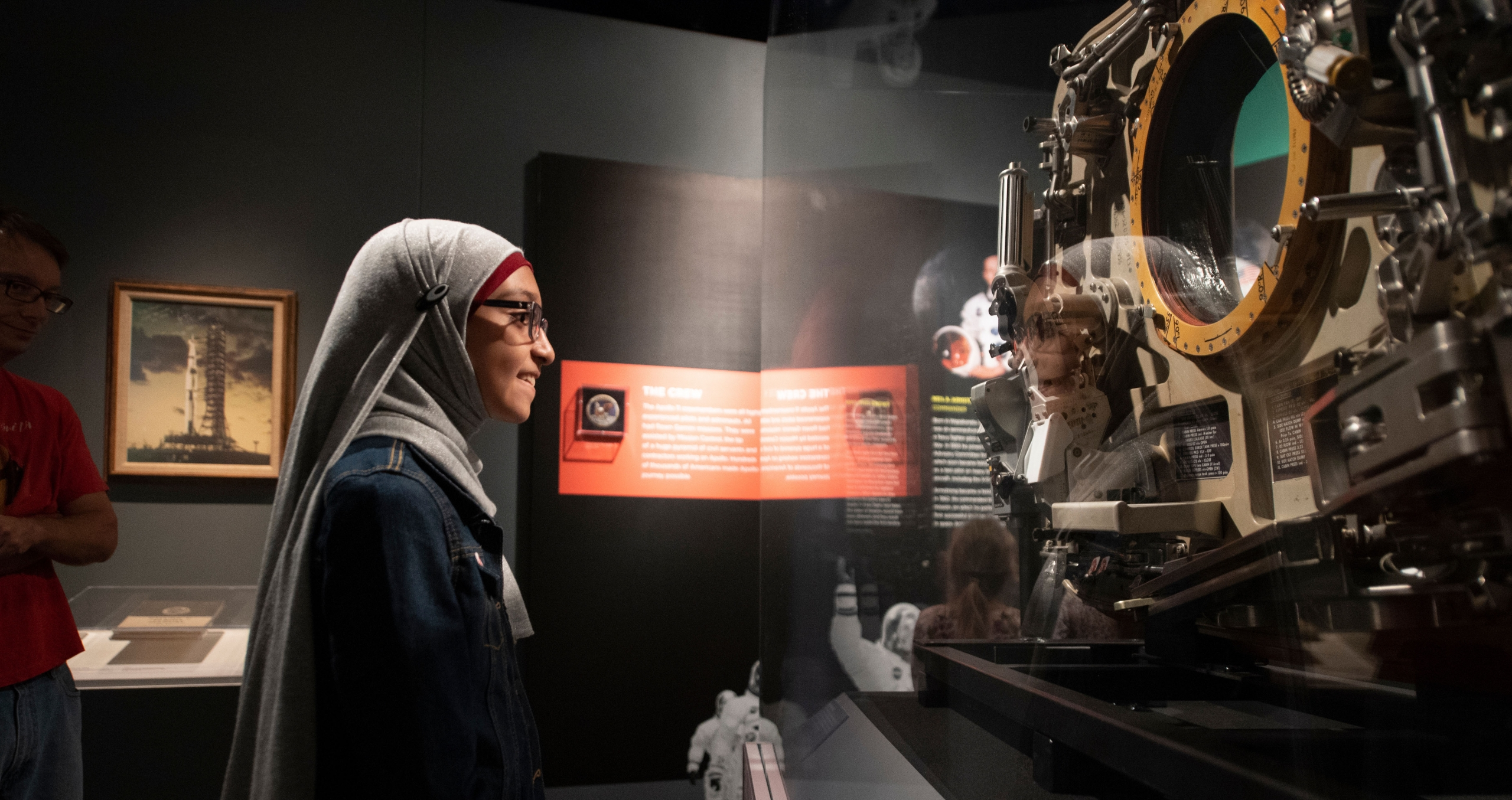 Female museum visitor looking at the Apollo 11 capsule