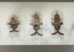 Three Alaskan masks hang on a gallery wall.