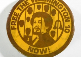 "A circular yellow button with brown graphic of an African American man behind bars with the words ""Free the Wilmington 10 Now!"" written around the edge of the button."