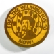 """A circular yellow button with brown graphic of an African American man behind bars with the words """"Free the Wilmington 10 Now!"""" written around the edge of the button."""