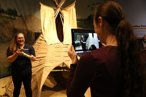 A woman holds a museum artifact while another films her on an ipad