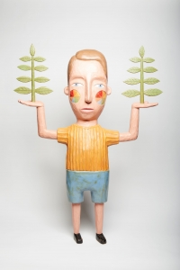An original wood sculpture of a man holding trees.