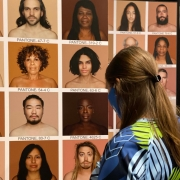A museum visitor looks at a display of various people of color.