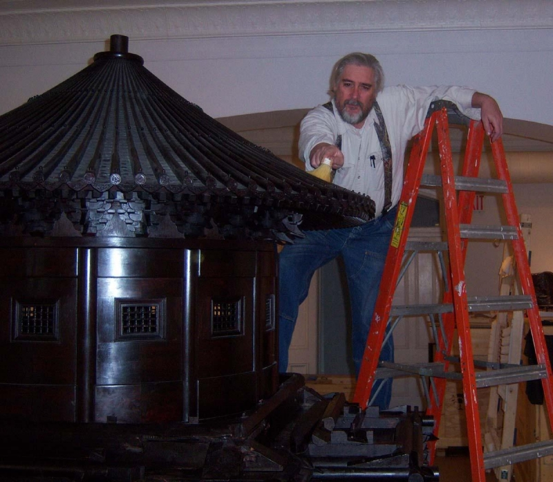 Expert Smithsonian furniture conservator Don Williams dusts the roof of the Pavilion.