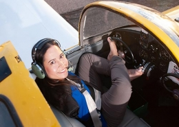 Jessica Cox sitting in cockpit of yellow airplane