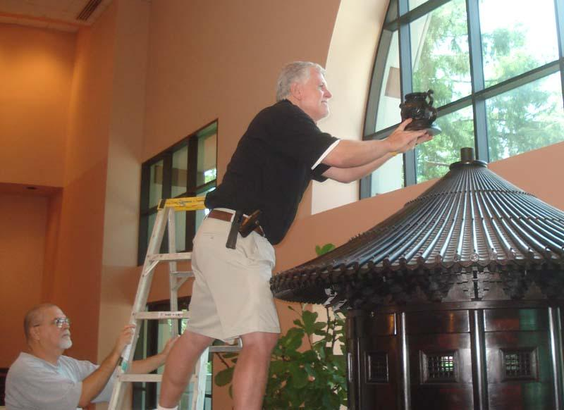 A volunteer carefully installs the top piece of the Pavilion.