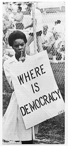 Woman holding a sign that reads Where is Democracy