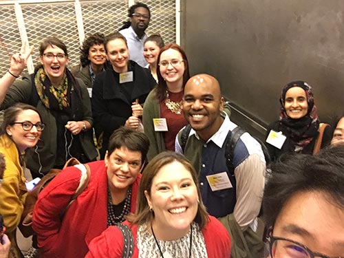 A group of people pose for a selfie in a large service elevator at a museum.