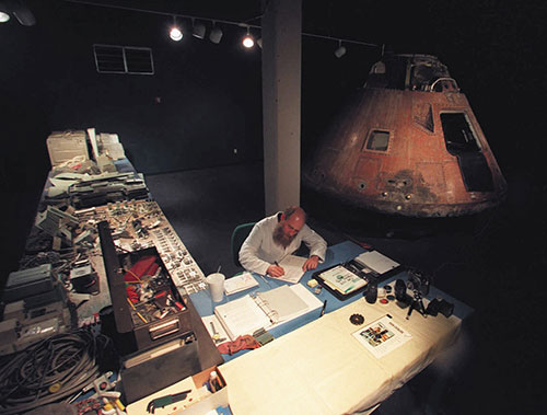 A person sits at a workshop desk with the Apollo 13 Odyssey command module in the shadows.