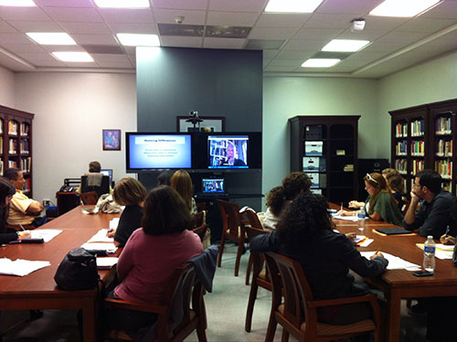 A group of people seated at two long tables in a library look at two monitors streaming a virtual lecture.