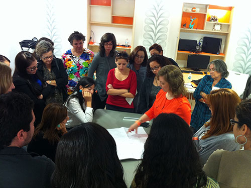 A group of people stand around a table where an instructor points at a document.