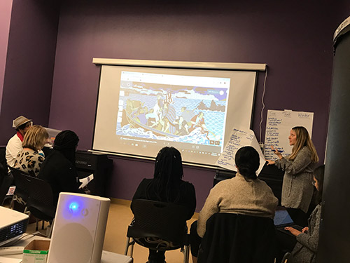 An instructor stands at the front of a classroom at an image on a screen.