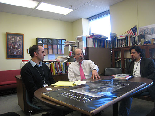 Three men sit at a table with a poster on top of it